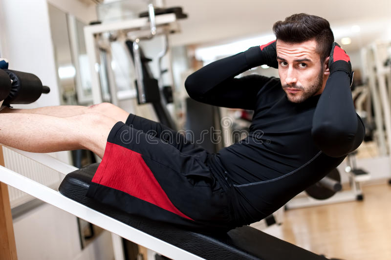 Handsome muscular man doing sit-ups on a incline bench. At fitness center and gym stock photos