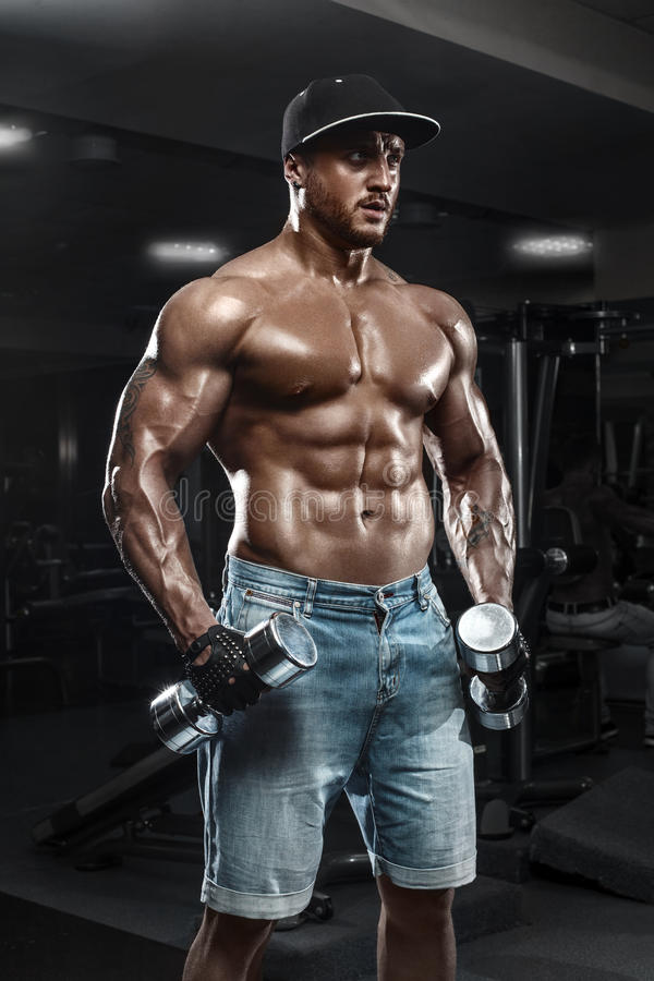 Handsome muscular man with dumbbells working out in gym, doing exercise royalty free stock photos