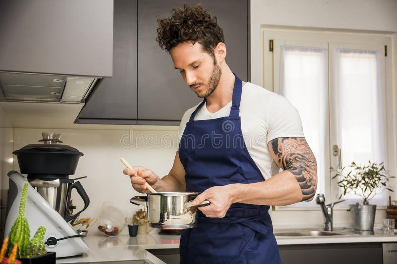 Handsome muscular man in kitchen, cooking. Handsome muscular man in kitchen at home, cooking at the stove stock photos