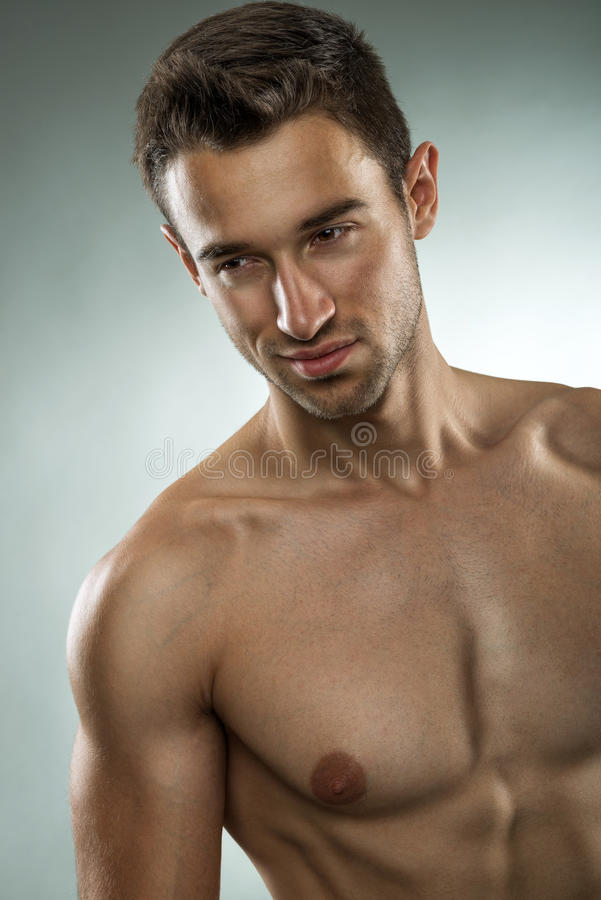 Handsome muscular man posing half naked, close-up photo stock image