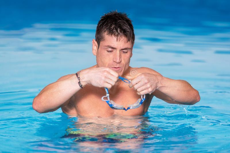 Handsome muscular man standing inside the pool putting on his swimming googles. royalty free stock photo