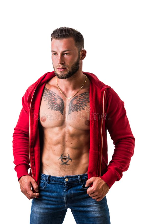 Handsome half-naked muscular man standing, isolated on white. Handsome muscular man with sweater open on naked torso, looking to a side, standing, isolated on royalty free stock photo