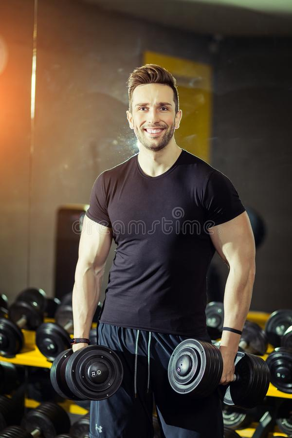 Handsome muscular man working out hard at gym royalty free stock photos