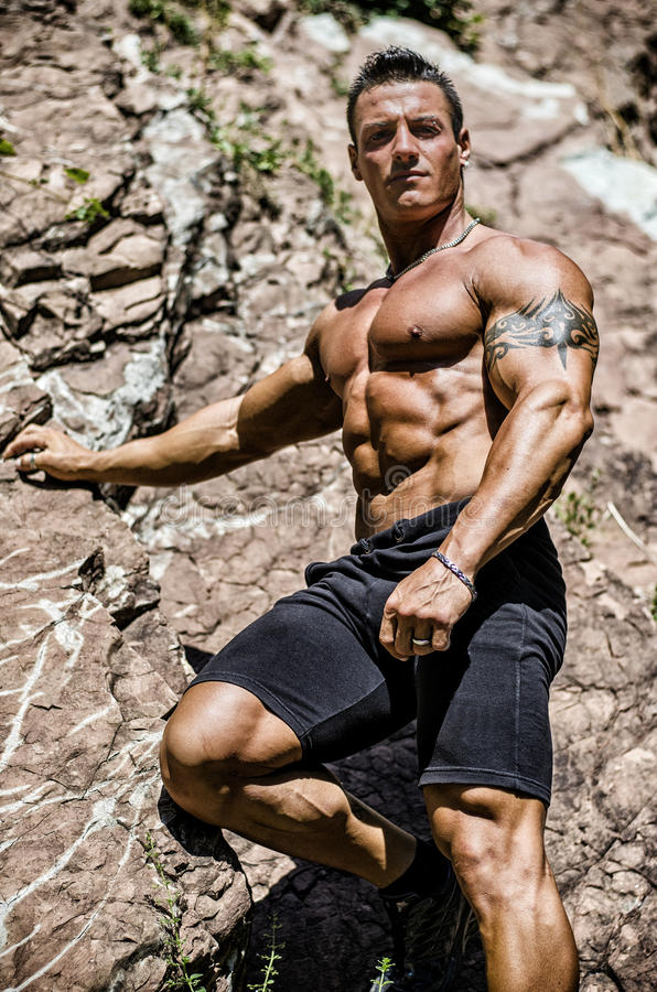 Handsome, muscular, shirless climber climbing rock stock photos