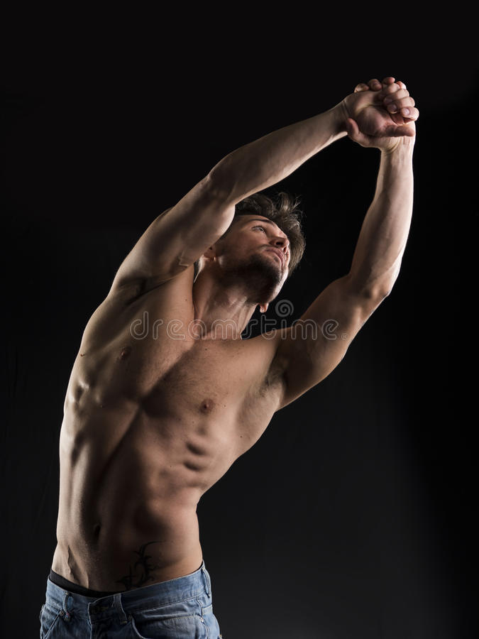 Handsome muscular shirtless young man stretching and looking up royalty free stock photography