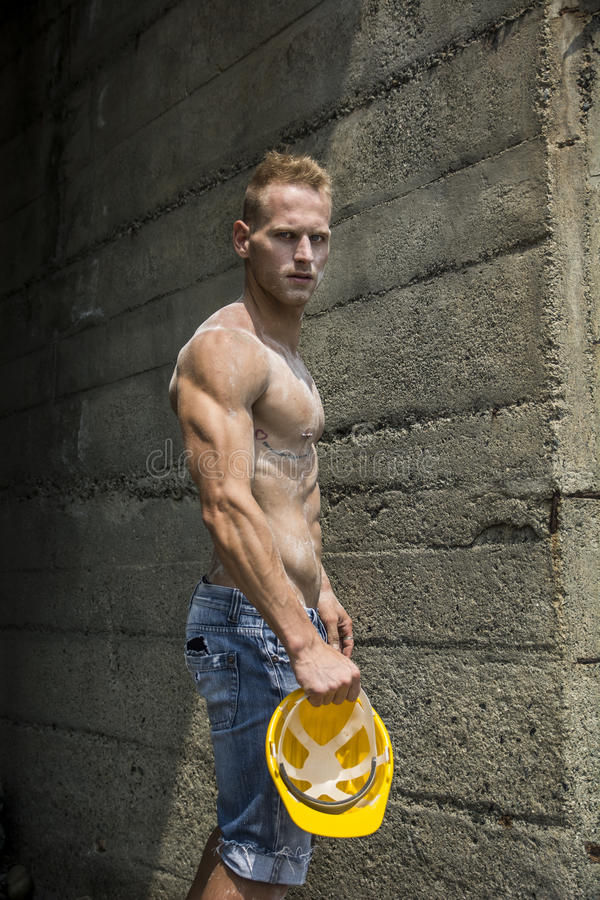 Handsome, muscular young construction worker shirtless outdoor stock image