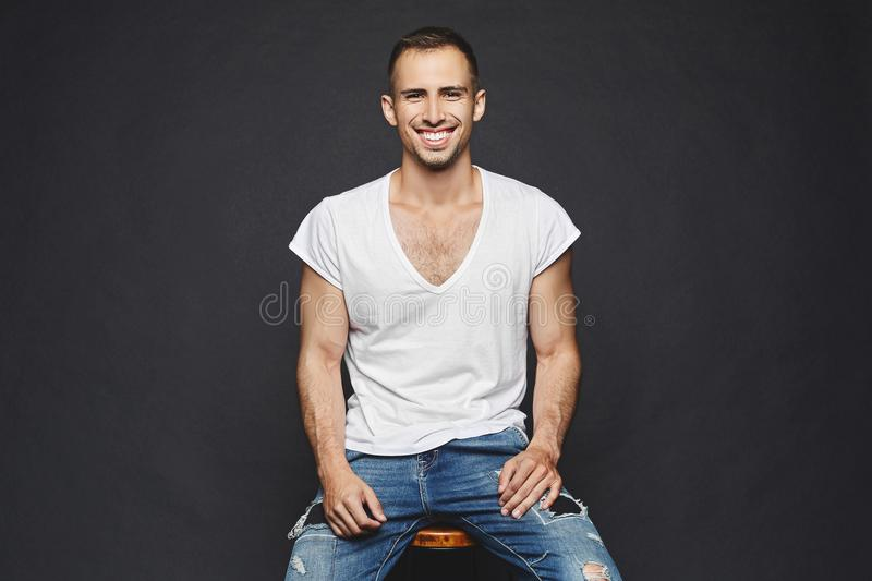 A handsome muscular young men with beard, in white t-shirt and in fashionable jeans sits on a chair, smiles and posing stock image
