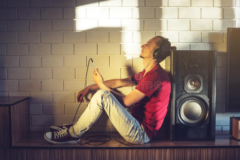 Handsome, a music lover listens to music with headphones with a mobile phone on the media and large speakers. stock image