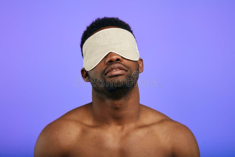 Handsome nacked man using sleeping mask stock image