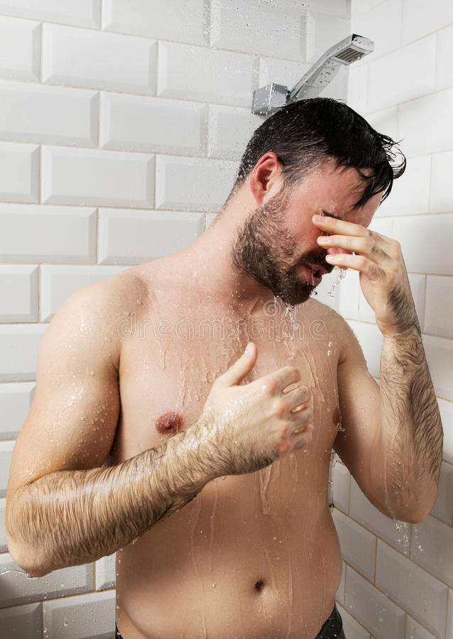 Handsome naked young man taking shower in bathroom royalty free stock photo