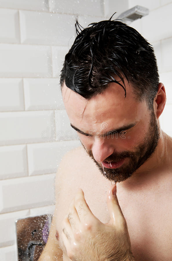 Handsome naked young man taking shower in bathroom stock image