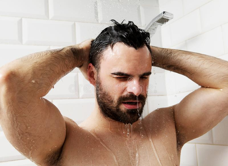 Handsome naked young man taking shower in bathroom stock photo