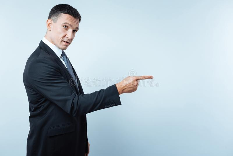 Handsome nice entrepreneur pointing in front of him royalty free stock photography