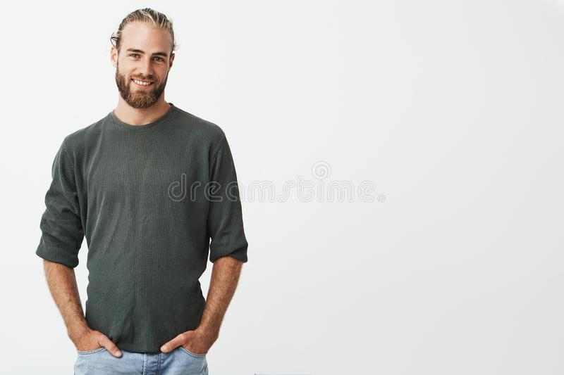 Handsome nordic man with beard and stylish hairstyle in grey shirt and jeans smiling, looking in camera, keeps hands in stock photos