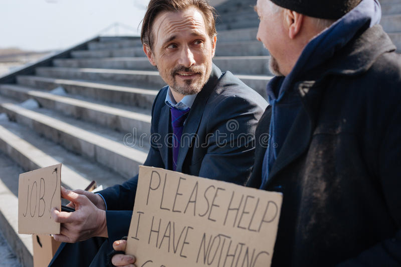 Handsome office worker looking for a job. True friend. Young men wrinkling his forehead keeping smile on his face while holding cardboard with notes royalty free stock image