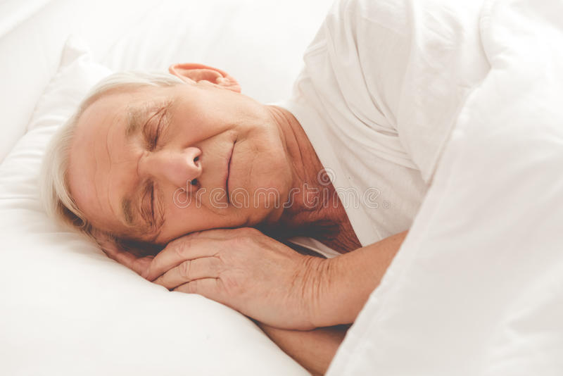 Handsome old man. Side view of handsome old man sleeping in bed stock photography