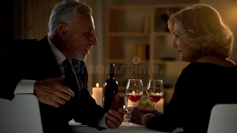 Handsome old man talking to woman in cafe, old friends conversation, dinner royalty free stock photo