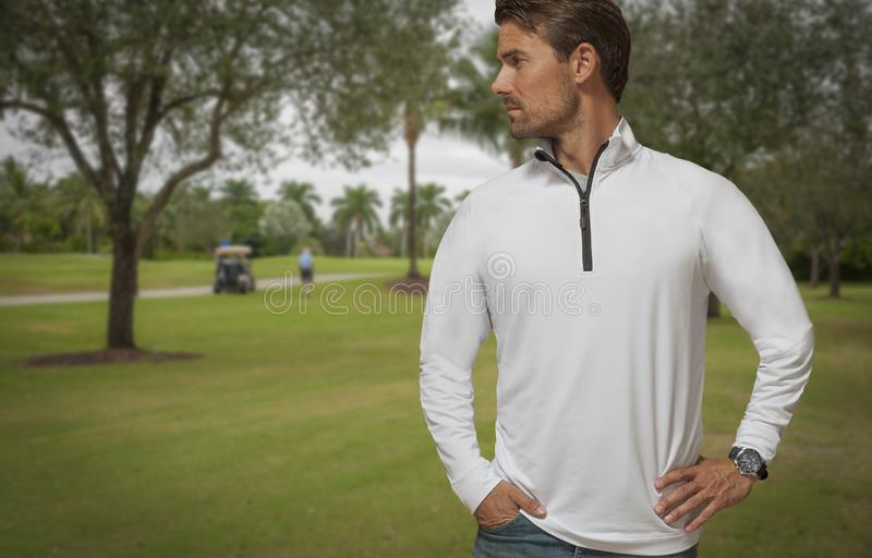 Handsome on-looker stands alone on the golf course looking away. stock photo