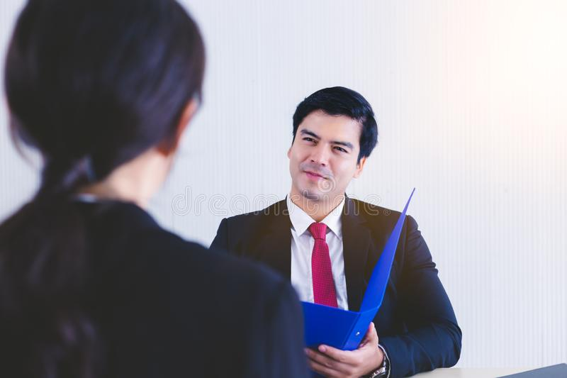 Handsome owner of company or senior businessman interviewing applicant, asking her experiences of working, reading resume in offic royalty free stock image