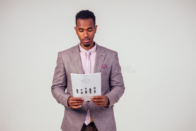 Handsome pensive Afro American Affessman in well-klädd grå kostym hold paper i studio på vit bakgrund arkivfoton