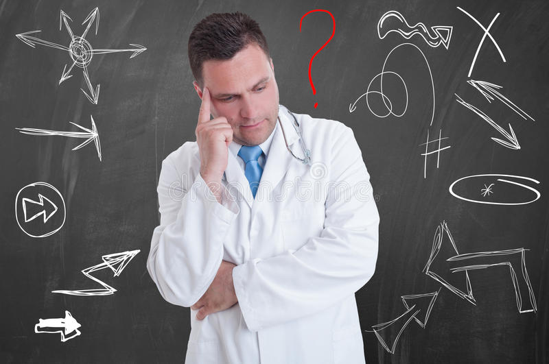 Handsome pensive doctor in a white coat contemplating stock photography