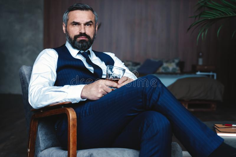 Handsome pensive man is touching his beard, looking away and thinking while sitting in armchair indoors. royalty free stock photo