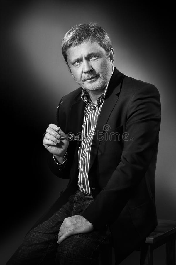 Handsome pensive mature businessman in formal suit is looking while sitting on chair, on gray background royalty free stock images