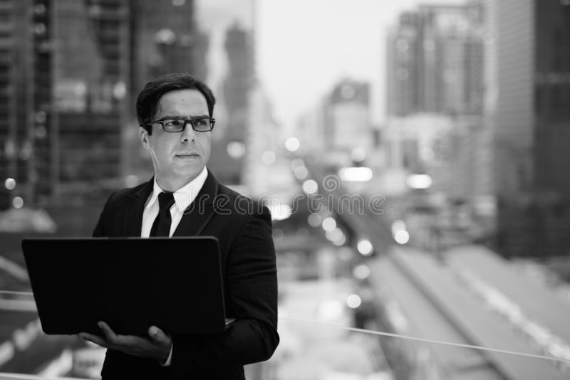 Handsome Persian businessman against view of the city in black and white stock photos