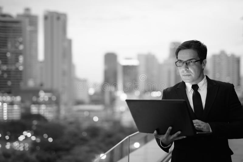Handsome Persian businessman against view of the city in black and white stock photography