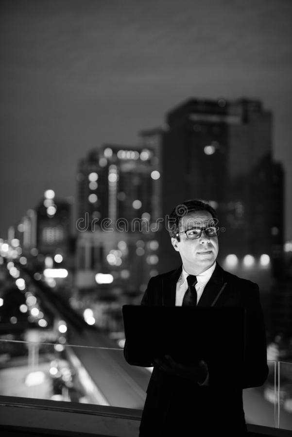 Handsome Persian businessman against view of the city at night royalty free stock photography