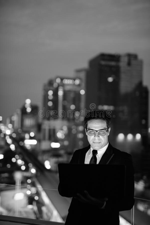 Handsome Persian businessman against view of the city at night royalty free stock photos