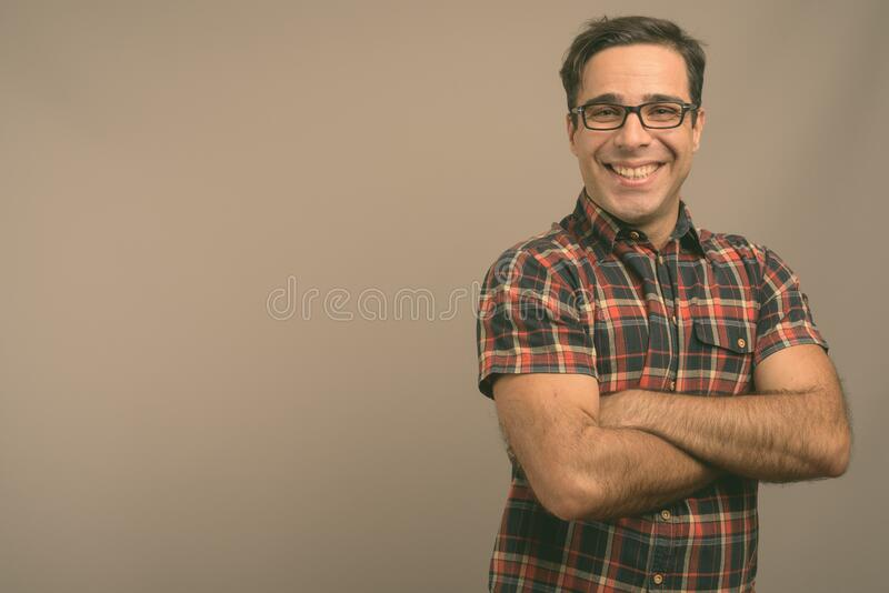 Handsome Persian man wearing eyeglasses against gray background stock images