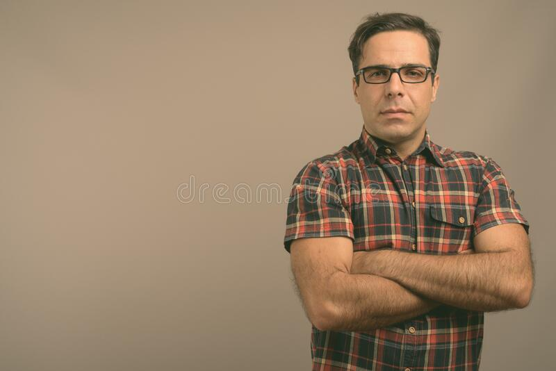 Handsome Persian man wearing eyeglasses against gray background stock photos