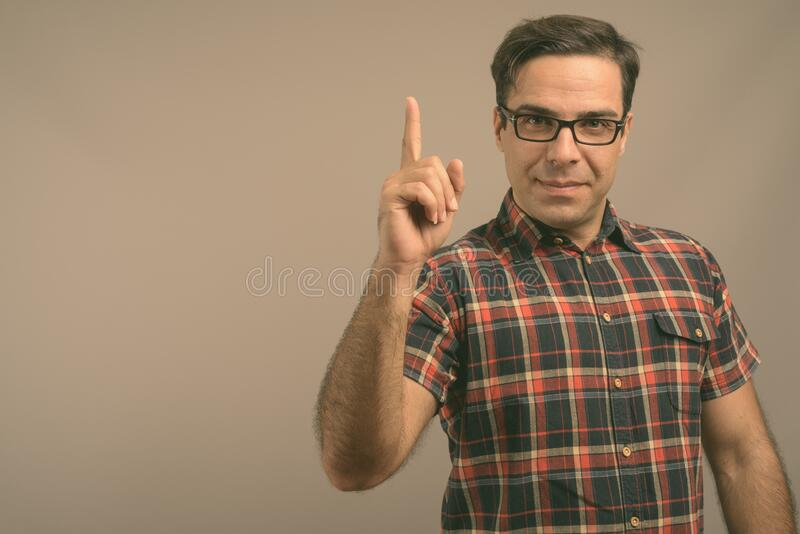 Handsome Persian man wearing eyeglasses against gray background stock photography