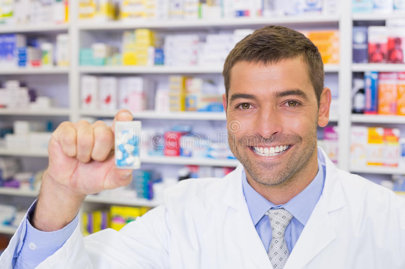 Handsome pharmacist showing medicine jar royalty free stock images