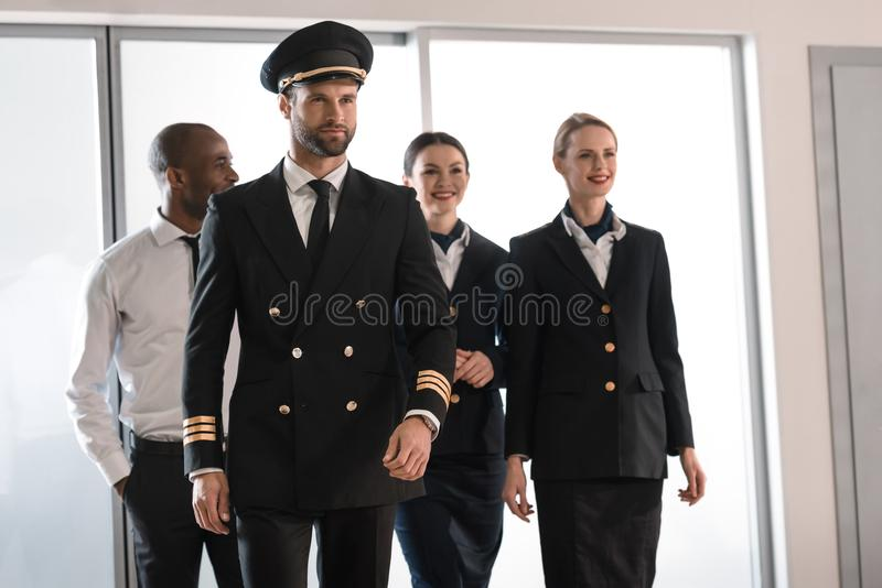 handsome pilot walking by airport royalty free stock photography