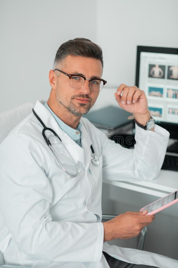 Handsome plastic surgeon sitting near the computer. Experienced plastic surgeon. Handsome experienced plastic surgeon wearing glasses sitting near the computer royalty free stock photos