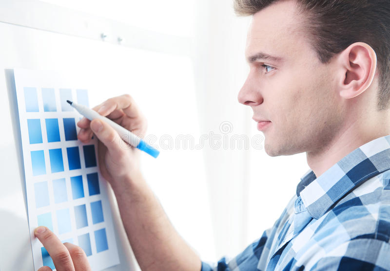Handsome pleasant man writing on the paper stock photography