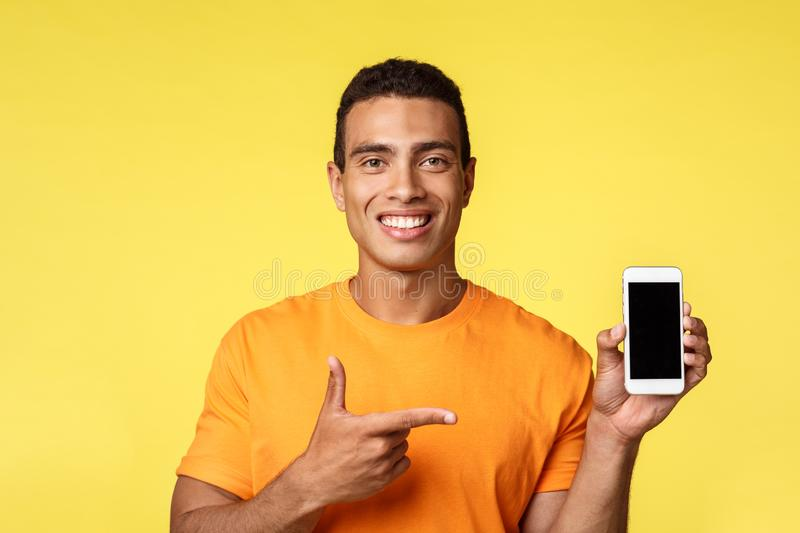 Handsome pleasant young man in orange t-shirt, holding smartphone pointing mobile display, smiling satisfied, recommend royalty free stock images