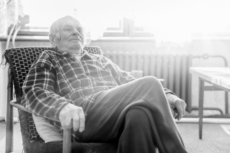 Handsome 80 plus year old senior man portrait. Black and white full body image of elderly man sitting in an armchair. stock image