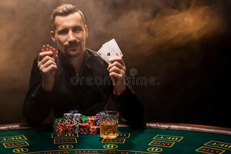 Handsome poker player with two aces in his hands and chips sitting at poker table in a dark room full of cigarette smoke stock photo