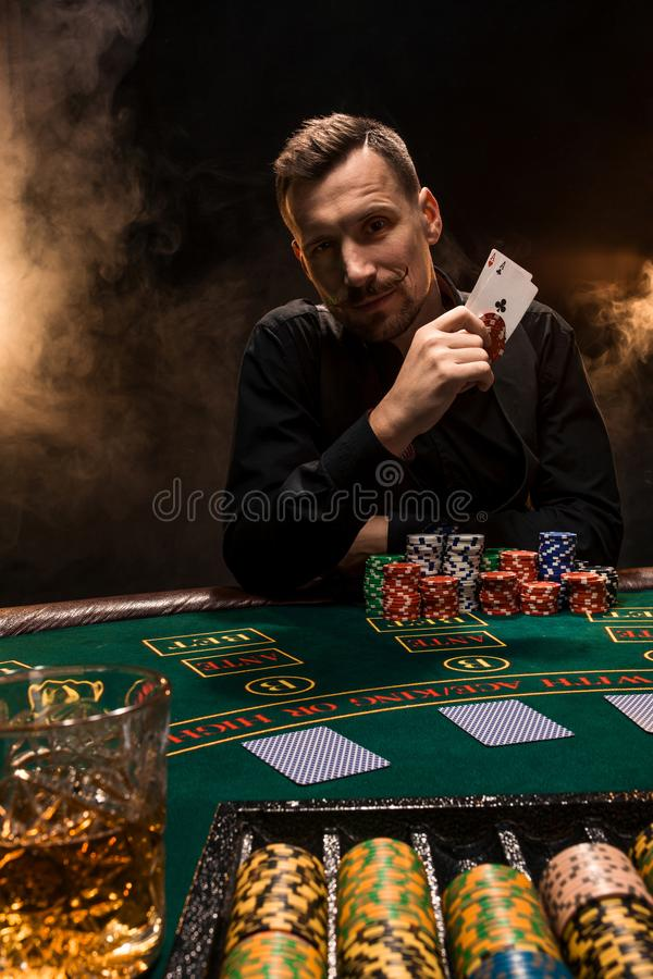 Handsome poker player with two aces in his hands and chips sitting at poker table in a dark room full of cigarette smoke stock image