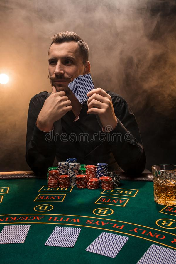 Handsome poker player with two aces in his hands and chips sitting at poker table in a dark room full of cigarette smoke royalty free stock photo