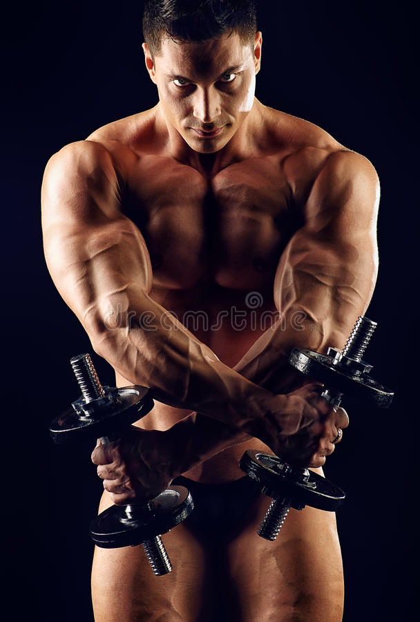 Handsome. Portrait of a handsome muscular bodybuilder posing with dumbbells over black background royalty free stock images