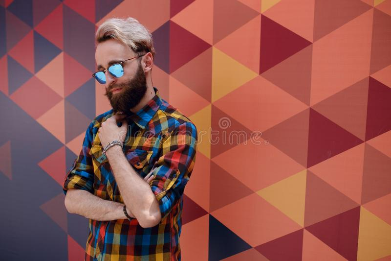 Handsome portrait of a young hipster man, posing near multicolore background, dressed in colorful shirt. stock images