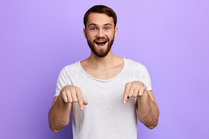 Handsome positive man pointing down with two fingers royalty free stock photography