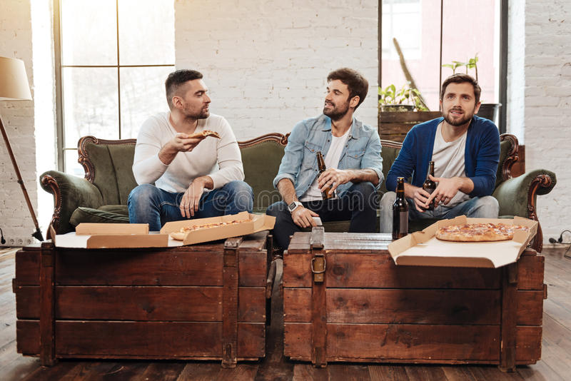 Handsome positive men looking at each other. Having a conversation. Handsome pleasant bearded men sitting on the sofa and looking at each other while resting stock photo