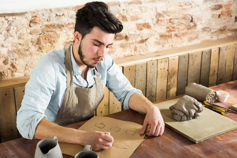 The handsome potter doing sketches of ware on the paper in his workplace. concept of small business, handcrafted work. Horizontal picture royalty free stock image
