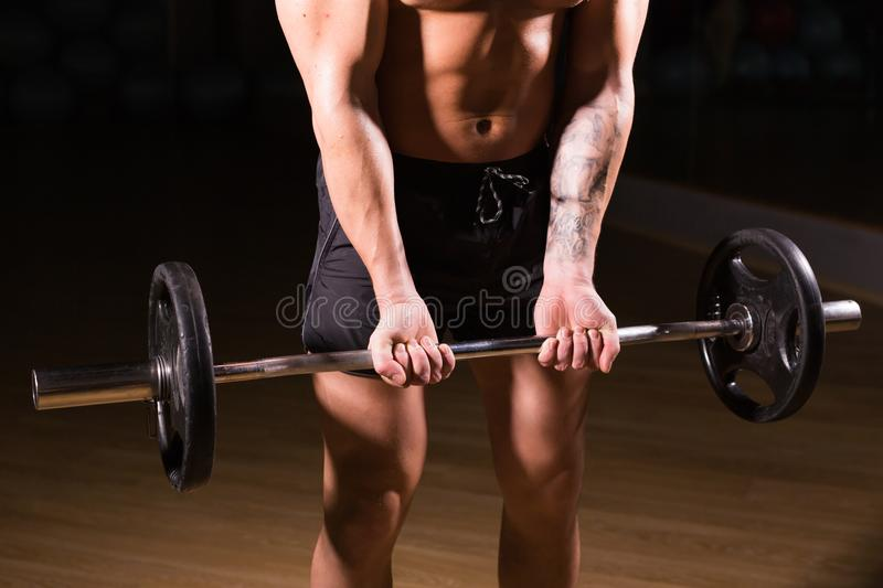 Handsome power athletic man with barbell. Strong bodybuilder with six pack, perfect abs, shoulders, biceps, triceps and stock image