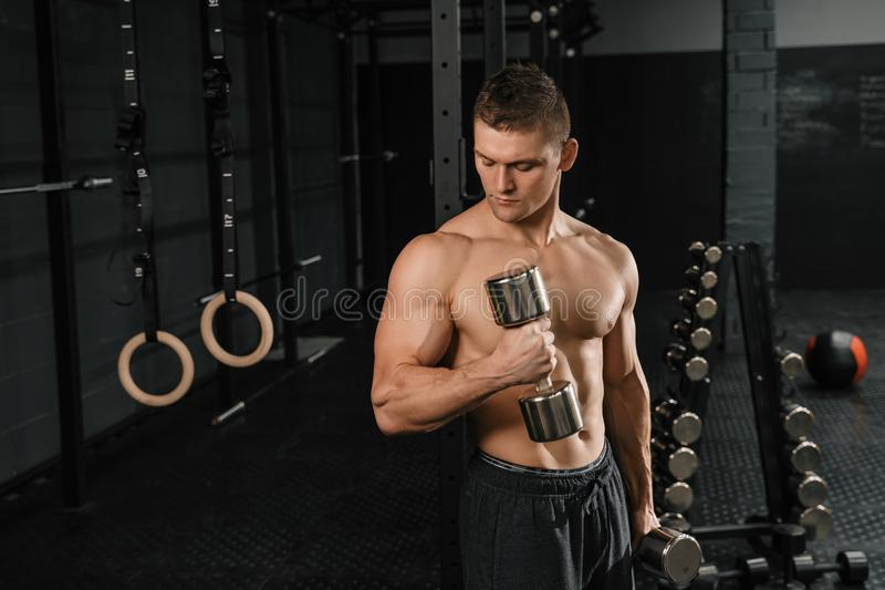 Handsome power athletic man bodybuilder doing exercises with dumbbell. In a gym. Fitness muscular body on dark background stock photography